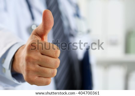 Male medicine doctor holding document pad in hand showing OK or approval sign with thumb up. High level and quality medical service, best treatment and patient care concept. Satisfied, happy intern