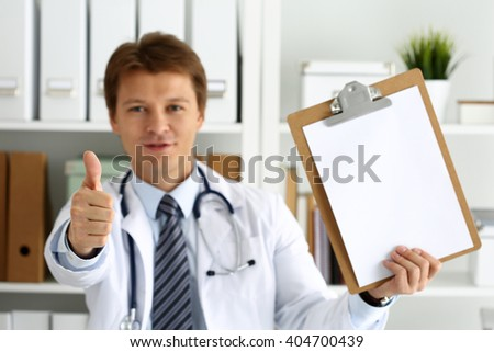 Male medicine doctor holding document pad in hand showing OK or approval sign with thumb up. High level and quality medical service, best treatment and patient care concept. Satisfied, happy intern - stock photo