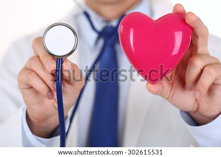 Male medicine doctor holding red heart and stethoscope head in front of chest closeup. Medical help, cardiology care, health, prophylaxis, prevention, insurance, surgery and resuscitation concept - stock photo