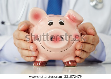Male medicine doctor wearing blue tie holding and covering happy funny smiling piggybank in hands closeup. Medical service economy, health care savings and insurance concept. Focus on piggy bank - stock photo