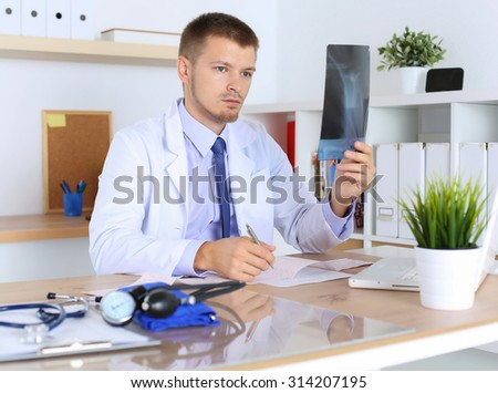 Male medicine physician doctor diagnosing patient with x-ray picture and cardiogram chart sitting at desk in office.  Radiologist, traumatologist or medical insurance concept. Therapeutist thinking - stock photo
