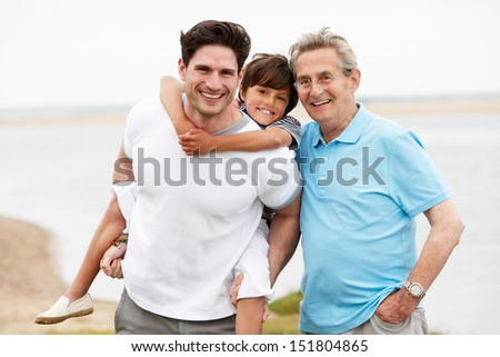 Male Members Of Multi Generation Family Standing By Sea - stock photo