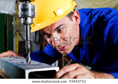 male metal worker using drillpress