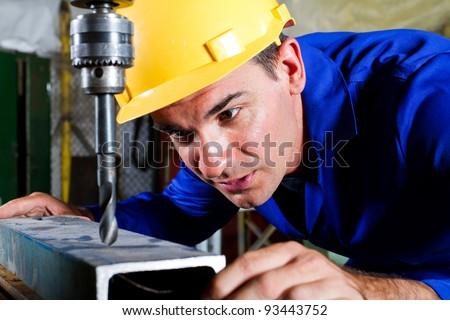 male metal worker using drillpress - stock photo
