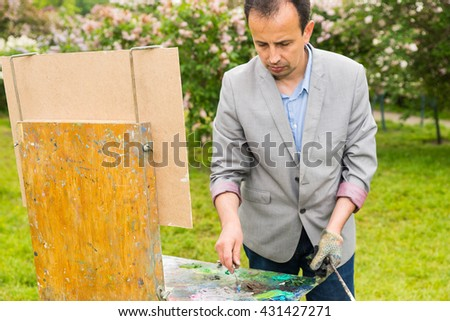 Male middle-aged concentrated creative artist working  on a trestle and easel painting with oils and acrylics during an art class in a park - stock photo