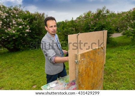 Male middle-aged creative artist standing in front of  a sketchbook during creation a sketch of his picture on a trestle and easel painting with oils and acrylics in the park or garden - stock photo