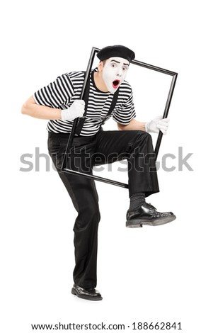 Male mime artist walking through a metal frame isolated on white background - stock photo