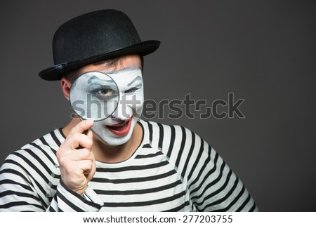 Male mime looking through the magnifying glass - stock photo