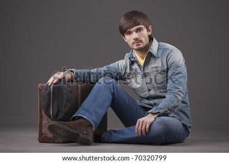 male model in denim clothes sitting on the ground with old suitcase - stock photo