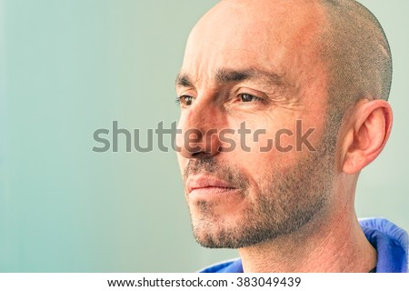 Male model in pensive mood - Thoughtful caucasian guy looking away - Middle age man with serious contemplative facial expression - Concept of human moods - Blurred background for text use - stock photo