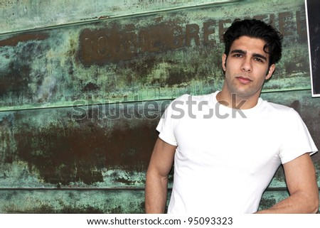 Male model in white shirt leaning against rusty green wall.
