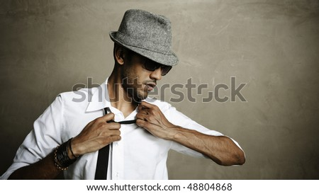 Male model is fed up with wearing a tie and pulls at his neck - stock photo
