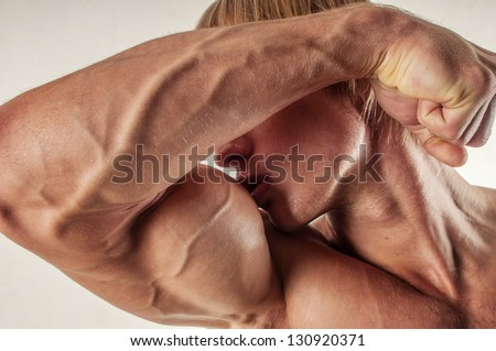 Male model kissing his biceps - stock photo
