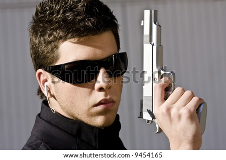 Male model performing secret agent with gun - stock photo