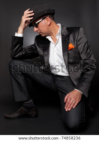 Male model poses in suit with his fedora