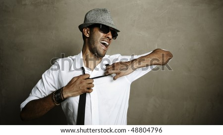 Male model pulls at his necktie in studio