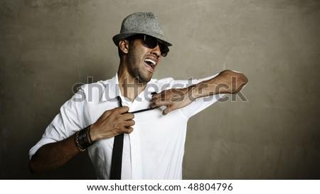 Male model pulls at his necktie in studio - stock photo