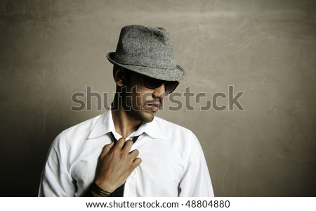 Male model stands in front of grunge wall deep in thought - stock photo