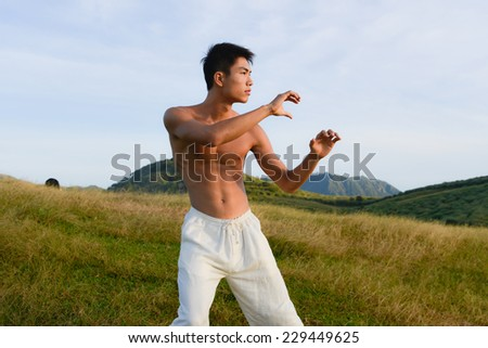 male model with muscles in exercise outdoors. over mountain grass