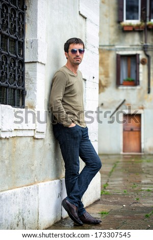 Male model with sunglasses posing on street - stock photo