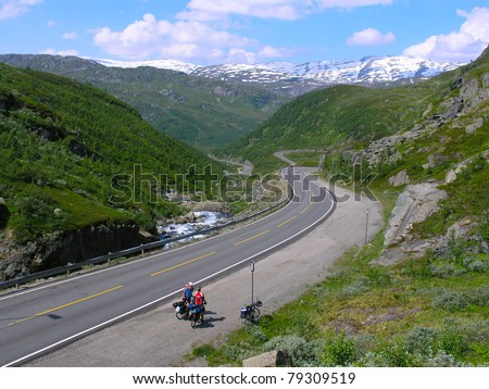 Male mountain bike cyclist riding uphill along a country road; clear summer day - stock photo