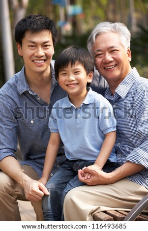 Male Multi Genenration Chinese Family Group Sitting On Bench In Park Together - stock photo