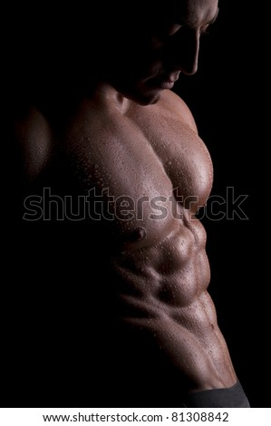 Male muscular body covered with water-drops