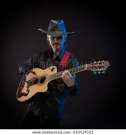 Male musician in black hat with guitar in hands playing and posing on black background in blue scenic light