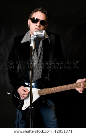 Male musician performing with guitar and retro mic - stock photo