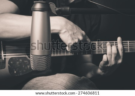 male musician playing acoustic guitar behind condenser microphone in recording studio, bw film filter - stock photo