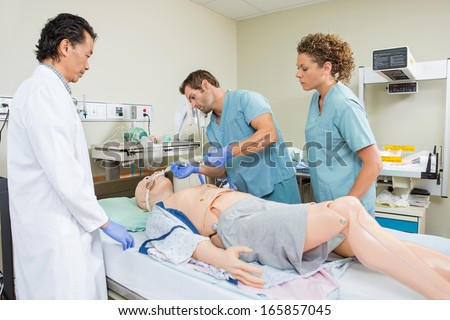 Male nurse adjusting endotracheal tube on dummy patient while colleague and doctor looking at it in hospital - stock photo