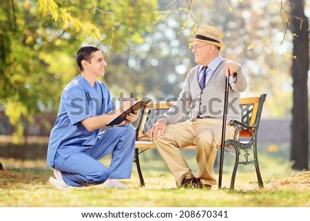 Male nurse and an elderly having a conversation in park  - stock photo