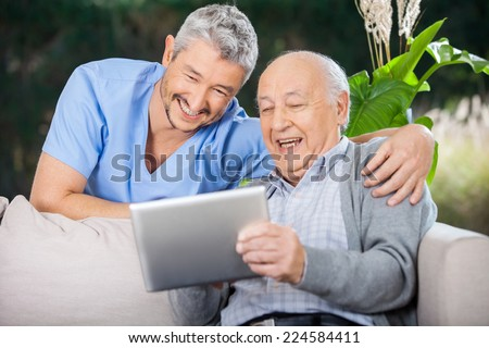 Male nurse and senior man laughing while looking at digital PC at nursing home porch - stock photo