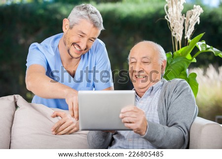 Male nurse and senior man laughing while using digital tablet at nursing home porch - stock photo
