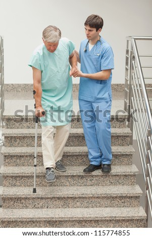 Male nurse assisting a patient on stairs in hospital - stock photo