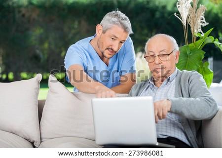 Male nurse explaining something on laptop to senior man at nursing home porch - stock photo
