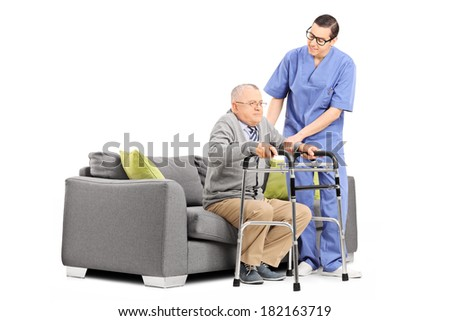 Male nurse helping an elderly gentleman to stand up isolated on white background - stock photo