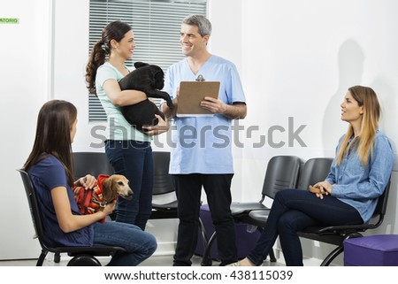 Male Nurse Holding Clipboard While Pet Owners Looking At Him - stock photo