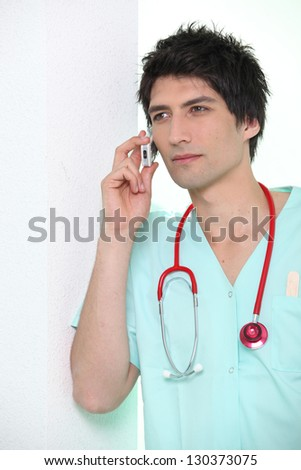 Male nurse leaning against wall holding  mobile telephone to ear - stock photo