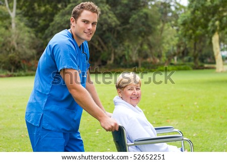 male nurse pushing a senior patient on wheelchair outdoors