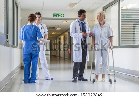 Male nurse pushing stretcher gurney bed in hospital corridor with doctors & senior female patient - stock photo