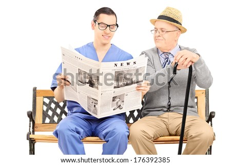 Male nurse reading a newspaper to an elderly gentleman seated on bench isolated on white background - stock photo