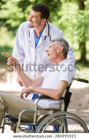 Male nurse talking with senior patient in wheelchair in garden near hospital. Side view. - stock photo