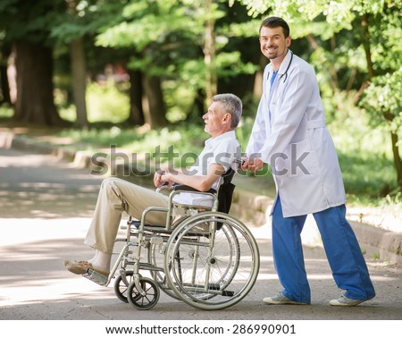 Male nurse walking with senior patient in wheelchair in garden near hospital. Side view. - stock photo