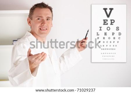 Male oculist doctor examining patient with an eye chart behind him. - stock photo