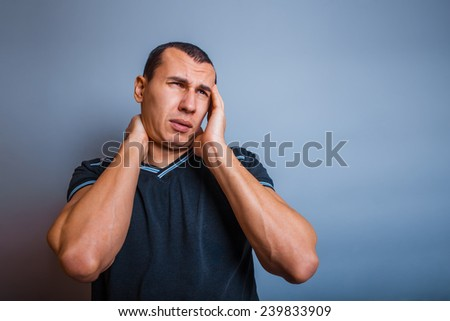 male of European appearance brunet holding his hand over his head, malaise - stock photo