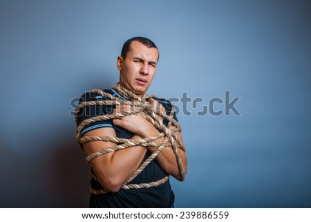 male of European appearance brunet tied with rope on a gray background - stock photo