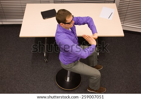 male office worker,exercising during short break in work at his desk in office - stock photo