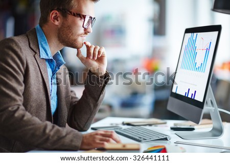 Male office worker looking at computer screen with data - stock photo