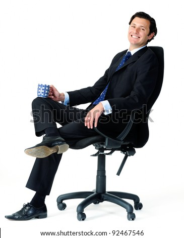 Male office worker relaxes on a chair, enjoying a cup of coffee - stock photo
